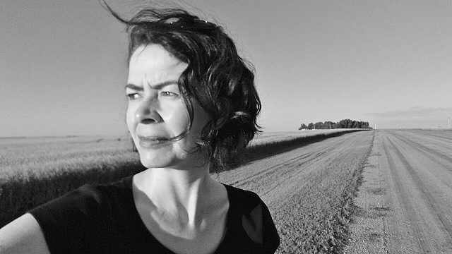 A woman, novelist Alissa York, stands beside a field of grain and an empty road.